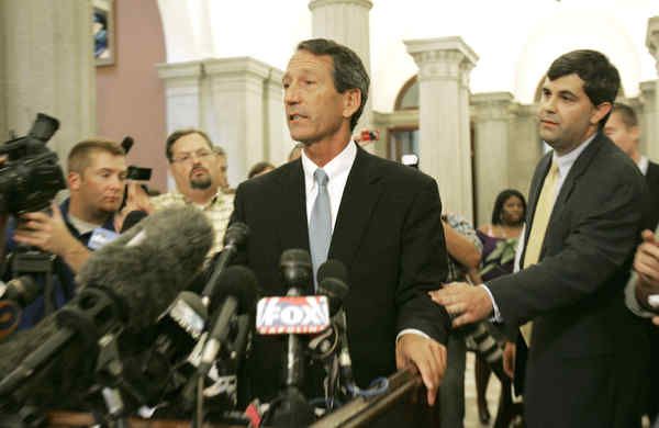 South Carolina Gov. Mark Sanford (center) answers reporters´ questions about his affair at a news conference.
