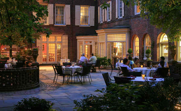 The tables of M Restaurant are in the bluestone courtyard of the Morris House Hotel on Eighth Street south of Walnut. Torches are lit after dark, and the dining area is shaded by genteel magnolias and towering holly. There are urns of petunias at the perimeter, and a skirt of boxwood.