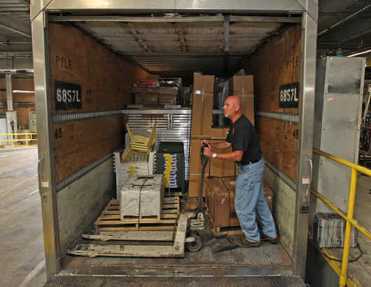"Truck driver Bob Pratt unloads his vehicle. Before the recession, he often experienced delays because deliveries were backed up. ""Now I back right in and I´m right out,"" he says."