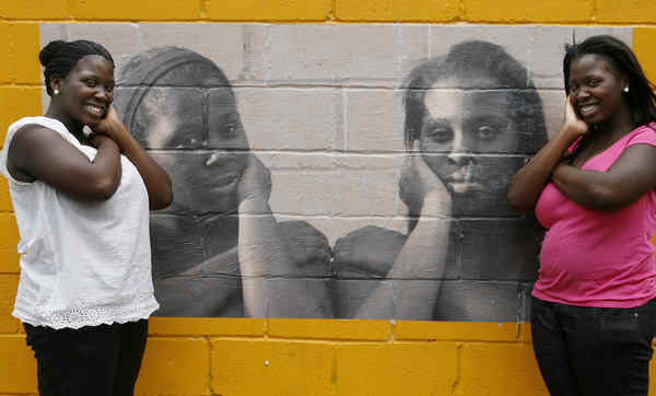 Identical twins Champayne (left) and Charmaine Barfield, 16, with their photo.