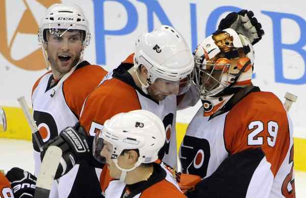 Ray Emery gets a pat on the mask by Braydon Coburn after Saturday win over Devils.