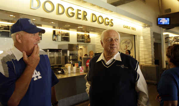 Former Dodgers manager Tommy Lasorda (right) walks past counter featuring the popular franks.