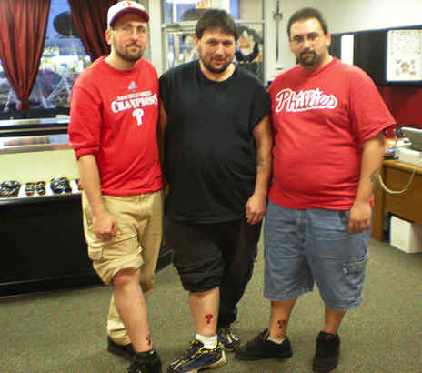 Showing off their free ink, courtesy of Flesh Effects in Allentown, are Phillies fans Robert Orendash Jr., Charles Ginkinger Jr. and Nick Dibucci, all of Allentown.