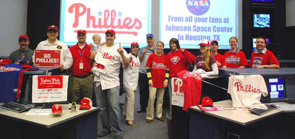 "Phillies fans working a long way from home at NASA´s Johnson Space Center in Houston cheer ""Go, Phils!"" (From left): Dan Dimarco, Jason Hutt, John Venditti, Baby Benjamin and dad Kevin Metrocavage, Melinda Refford, Stephen Tripodi, Erica Nyman, Chloe Abraczinskas, Christine Furgione, Ken Neiss, Beth Weissinger and Derek Sollosi."