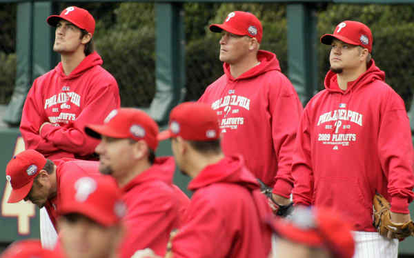 Phillies pitchers (from left) Cole Hamels , Tyler Walker and Joe Blanton hang out in the outfield during a workout at the Bank.