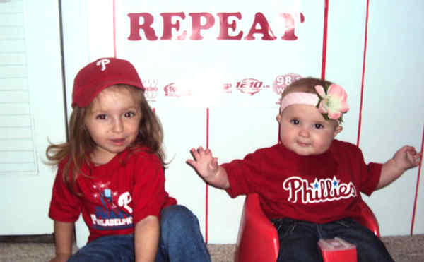 Grace Walsh (left), 2, and sis Finnley, 7 months, discussed their hopes for a Phillies win in their Havertown basement recently. Both agreed they did not want to wait another 28 years for a championship. Parents Jen and Dan Walsh, lifelong Phillies phanatics, agree.