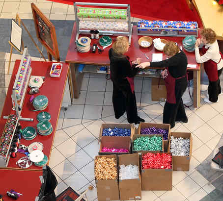 Volunteers from the Marlyn Fein chapter of the Fox Chase Cancer Center wrap gifts for donations at the Willow Grove Park Mall on Wednesday.