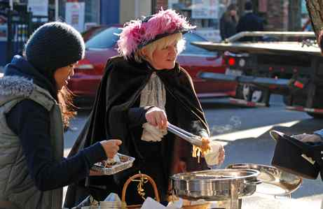 """Looking as if she stepped from a Dickens story, Jackie Arzymanow, above, serves """"English"""" Pad Thai Stew while Arin Sararam digs into a serving of mince tart. Some of the tiny tarts, below - more authentically English - were made by Arzymanow from a jar of her own mincemeat."""