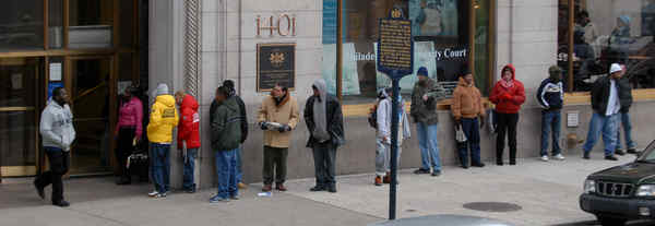 People with business to conduct in Philadelphia Community Court wait on Arch Street for it to open. Though instructed to show up at 8:30 a.m., they could not enter until after 8:50. New rules will tell them to show up at 9.