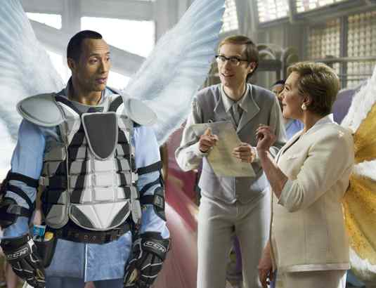 Dwayne Johnson as the new tooth fairy, getting instructions from his Fairy-land caseworker (Stephen Merchant) and the boss (Julie Andrews).