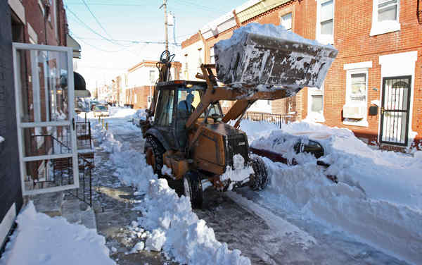 No business like snow business: Jeff Toal carefully clears snow with a front-end loader from diminutive Daly Street in S. Phila.