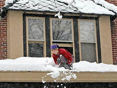 In Phoenixville, Laura Wildman clears heavy snow off her roof on Wednesday, Feb. 10, 2010. But there is a bright side to all the white stuff. (Steven M. Falk / Staff Photographer)