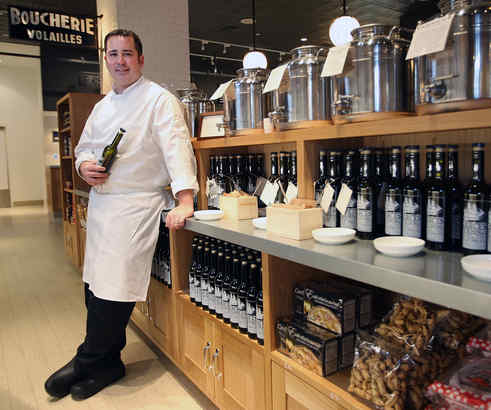 Adam DeLosso, chef de cuisine and general manager at Garces Trading, with olive oil canisters ready for customers to fill their own bottles at the market-cafe-wine boutique, a novel Pennsylvania hybrid.