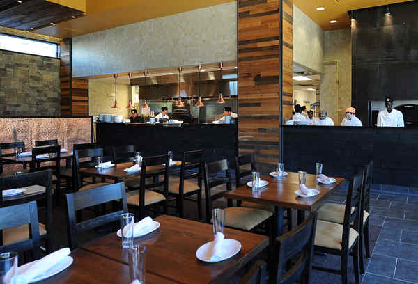 The mountain-lodge look of City Tap House, 3925 Walnut St., includes an open kitchen in the 120-seat main dining room.