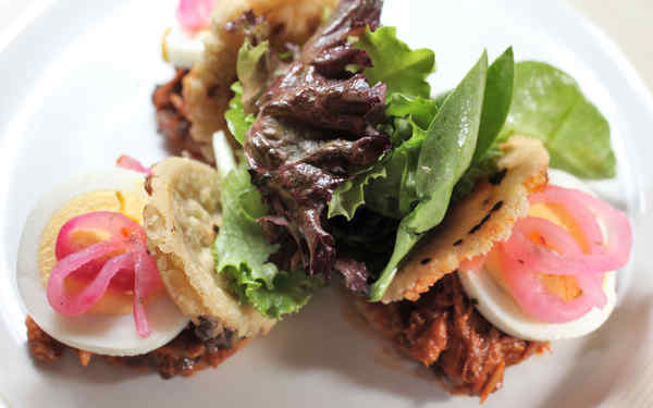 One of Jimenez´ gorditas, open-faced with pork, sliced hard-cooked egg, and pickled onion.