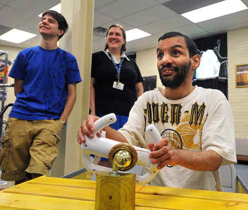 Dennison Perez steers a Wii game at United Cerebral Palsy. With him are student Greg Lobanov, who helped test the adapted controller Perez is using, and Springside physics teacher Ellen Kruger.