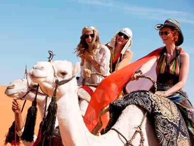 "Sarah Jessica Parker, Kim Cattrall and Cynthia Nixon climb aboard camels in ""Sex and the City 2."" (Warner Bros. Pictures)"