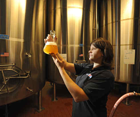 Whitney Thompson holds up a beaker of Prima Pilsner, inspecting its clarity during the brewing process at Victory Brewing Co. in Downingtown. Above, she stands behind a row of taps in the company restaurant.