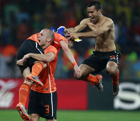 The Netherlands´ Johnny Heitinga hoists Wesley Sneijder as Giovanni van Bronckhorst joins in after the 2-1 win over Brazil.