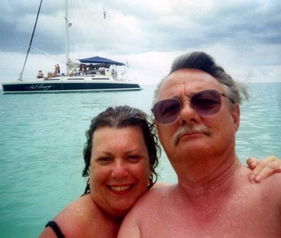 The writer, Barbara Jones, and her husband, David, on the beach. The catamaran of partyers they befriended is in the background.
