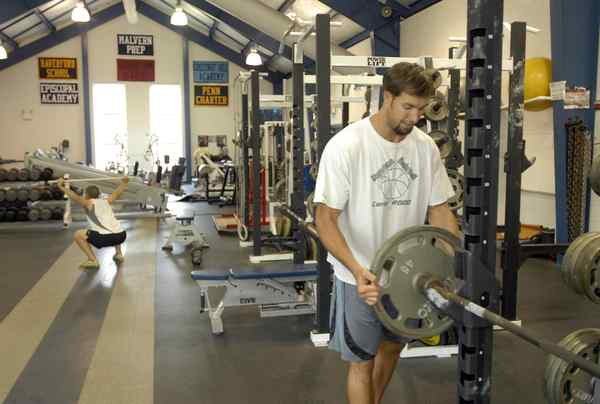 Erik Miller, a Malvern coach, loads iron in Malvern Prep´s strength-and-conditioning center.