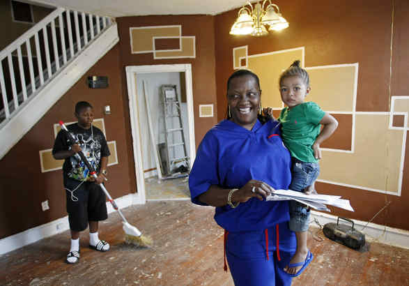 "Joan Porterfield, with son De´Onte (left) and granddaughter Aniya Scott, checks mail at her house. When officials closed Robert Stinson Jr.´s firm, Life´s Good, for alleged investment fraud, they said it had no ""significant"" property holdings."
