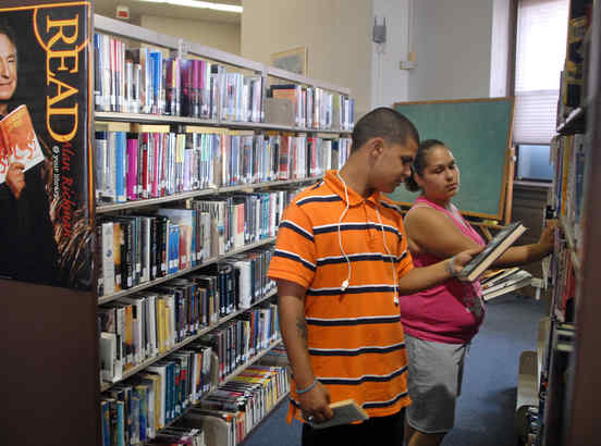 Pedro Munoz, 17, and Yani Munoz, 15, search the stacks for summer reading assignments in the Camden Free Public Library. The branch is in danger of closing after budget cuts.