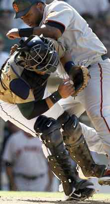 Contact sport: Padres catcher Yorvit Torrealba is bowled over by the Giants´ Pablo Sandoval, trying to score on Juan Uribe´s single in the eighth inning. Torrealba held onto the ball for the out.