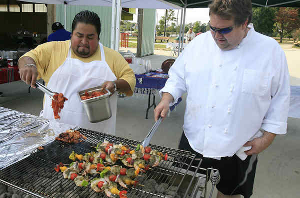 Saul Cordova, from La Esperanza in Lindenwold, cooks pork while Fred Kellermann, from Elements Cafe in Haddon Heights, works on his shrimp kebab.