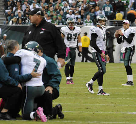 Armed and hammered: Kevin Kolb glances over on his way into action as the injured Michael Vick is aided.