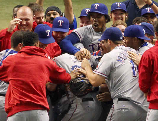 Cliff Lee is swarmed by Texas teammates after victory over Rays.