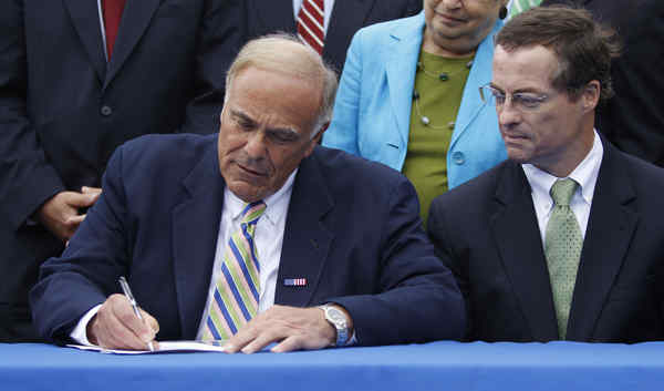Gov. Rendell signs an order banning new leasing of state forests for gas drilling. State official John Quigley is at right.