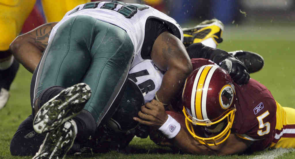 Eagles defensive linemen Brodrick Bunkley (97) and Trent Cole fight Donovan McNabb for a second-quarter fumble.