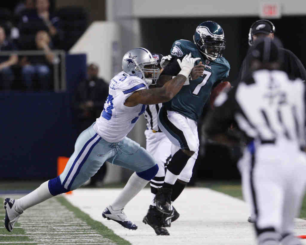 Michael Vick is pushed by the Cowboys´ Anthony Spencer , above, as he steps out of bounds. Below, Eagles coach Andy Reid complains to officials that no flag was thrown on the play.