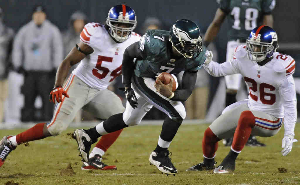 The Eagles´ Michael Vick is hemmed in by Giants safety Antrell Rolle (right) and linebacker Jonathan Goff in the Nov. 21 game.
