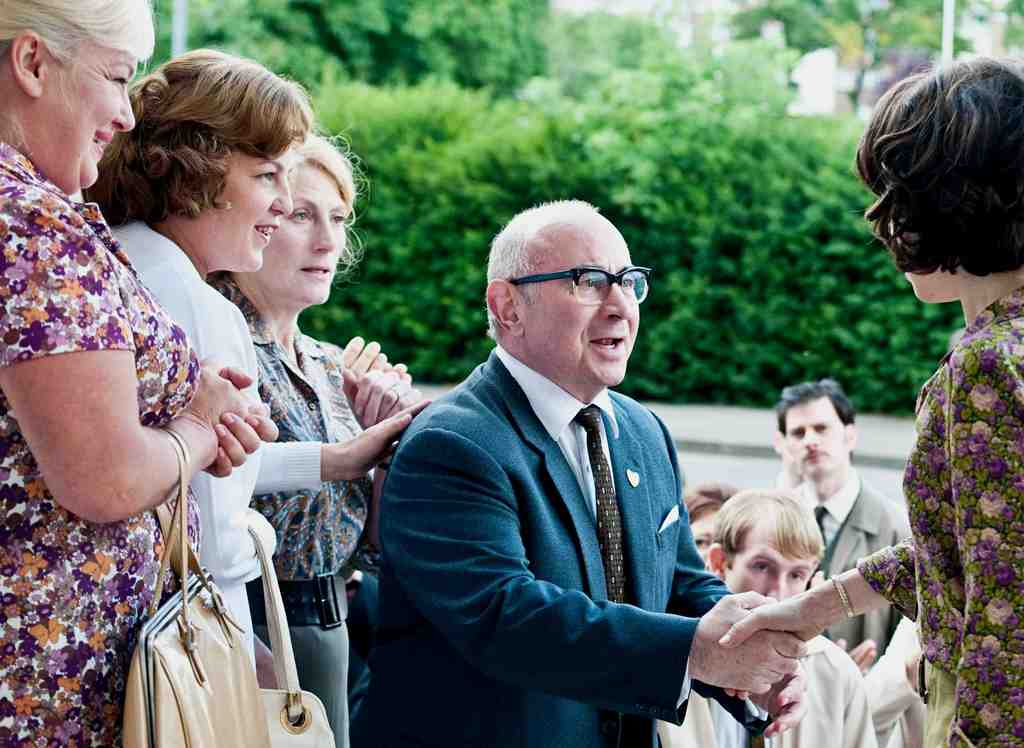 Bob Hoskins and Sally Hawkins shake hands in a scene that also features (from left) Nicola Duffett, Lorraine Stanley, and Geraldine James.