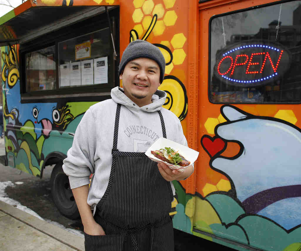 Owner Tyson Wong Ophaso displays a steamed pork bun as he stands in front of his truck.