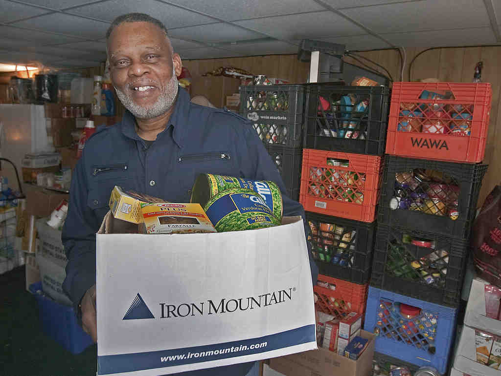 Derek Felton holds a box of food in his Philadelphia basement, where he is temporarily storing items for low-income residents.
