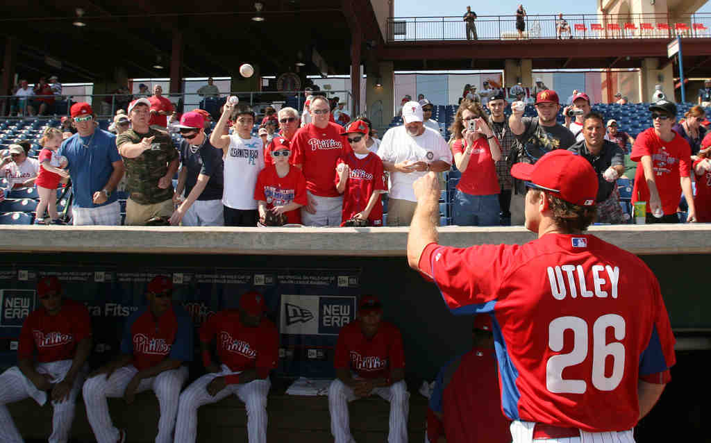 Chase Utley tosses back a baseball after signing an autograph at Bright House Field in Clearwater.