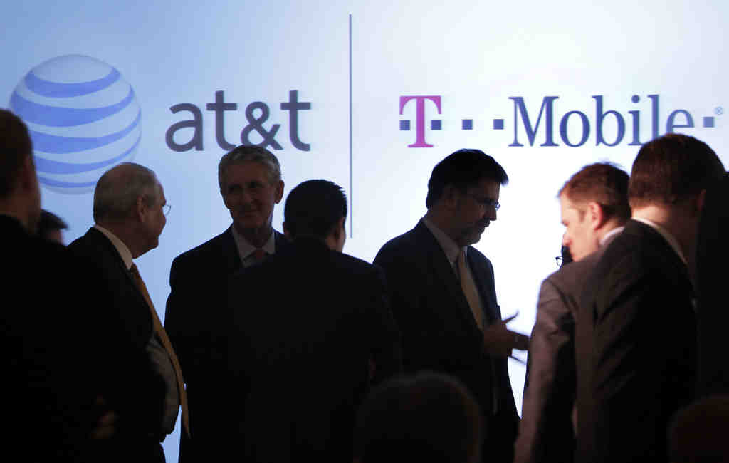 People gathering before an AT&T news conference Monday in New York. AT&T Inc. said Sunday that it would buy T-Mobile USA from Deutsche Telekom in a cash-and-stock deal valued at about $39 billion that would make it the largest U.S. cell phone firm.