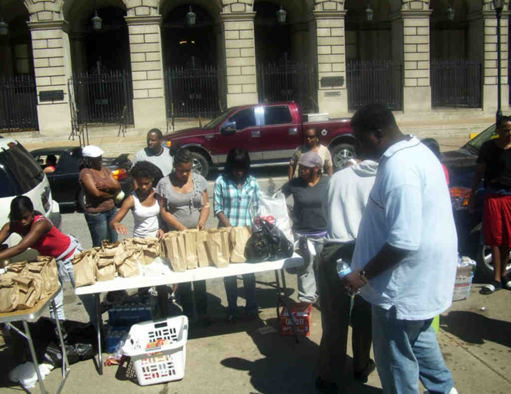 Craig Stroman (right) and other volunteers set out food on Vine Street outside Family Court as part of the efforts of his We Feed the Homeless Philly nonprofit.