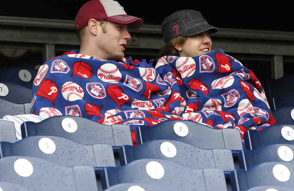 Chris Brookens and Alexis Klair, both 27, await the start of yesterday´s game huddled under the Phillies blanket she made for him for Christmas. In the windy afternoon chill, they needed it.