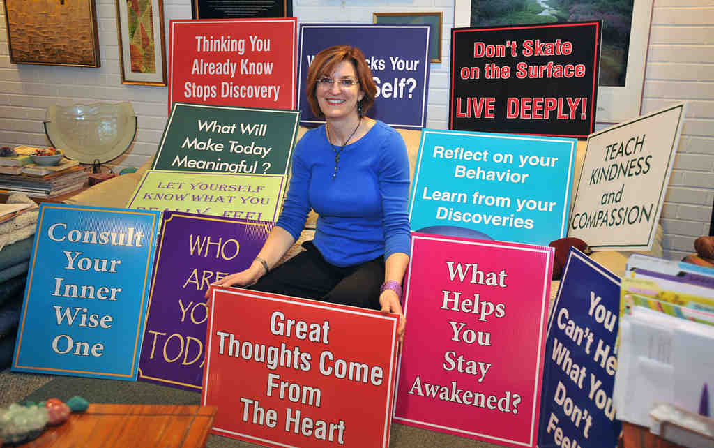 Meg Miller with some of her signs. A licensed psychologist, she intends to add 10 signs to her current collection of 40.