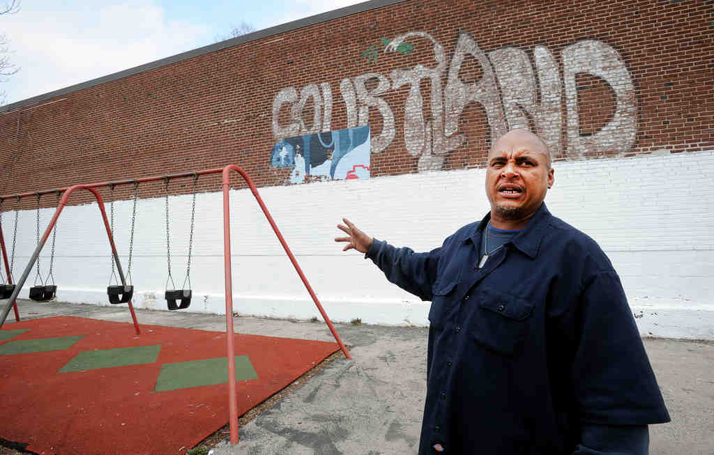At the Cecil B. Moore Recreation Center in N. Philadelphia, facilities caretaker Verland Wayns shows the wall that was painted over in preparation for a new mural. The community had little input before.