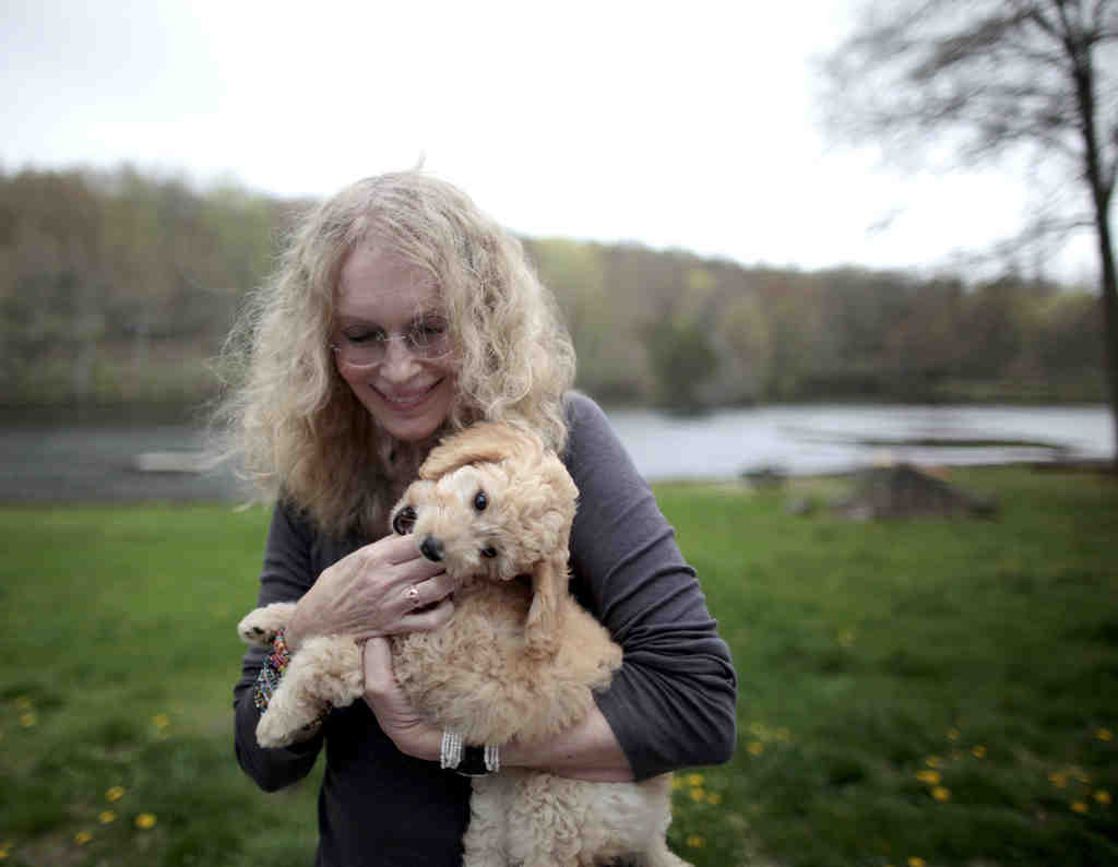 "Mia Farrow, with her dog, Maggie, is a UNICEF ambassador who has traveled to Angola, Sudan, and Nigeria on humanitarian missions. ""I think if you see something that needs doing and you can - you do it,"" she says."