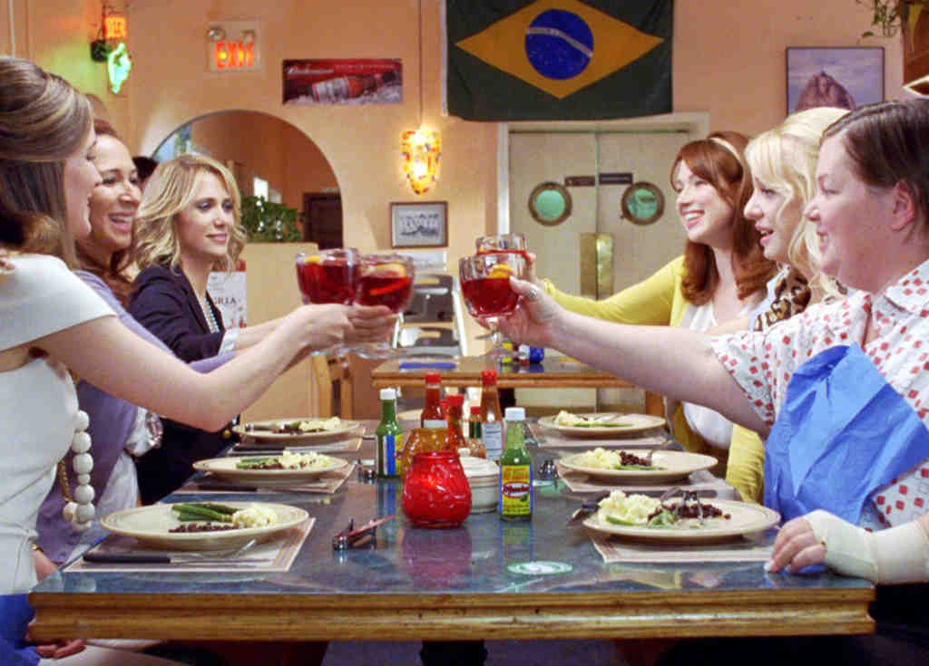 Sharing a meal are, from left, Ellie Kemper, Maya Rudolph, Kristen Wiig, Rose Byrne, Wendi McLendon- Covey, and Melissa McCarthy.