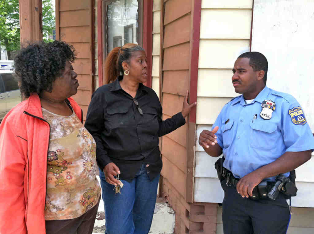 In the Hartranft neighborhood, activists Diane Bridges (left) and Arnetta Curry talk with police Officer Tyshaan Williams.
