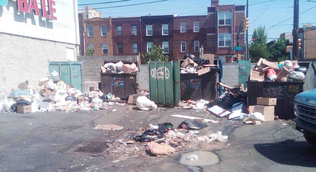Trash overflows from bins at the New World Shopping Plaza in South Philly.