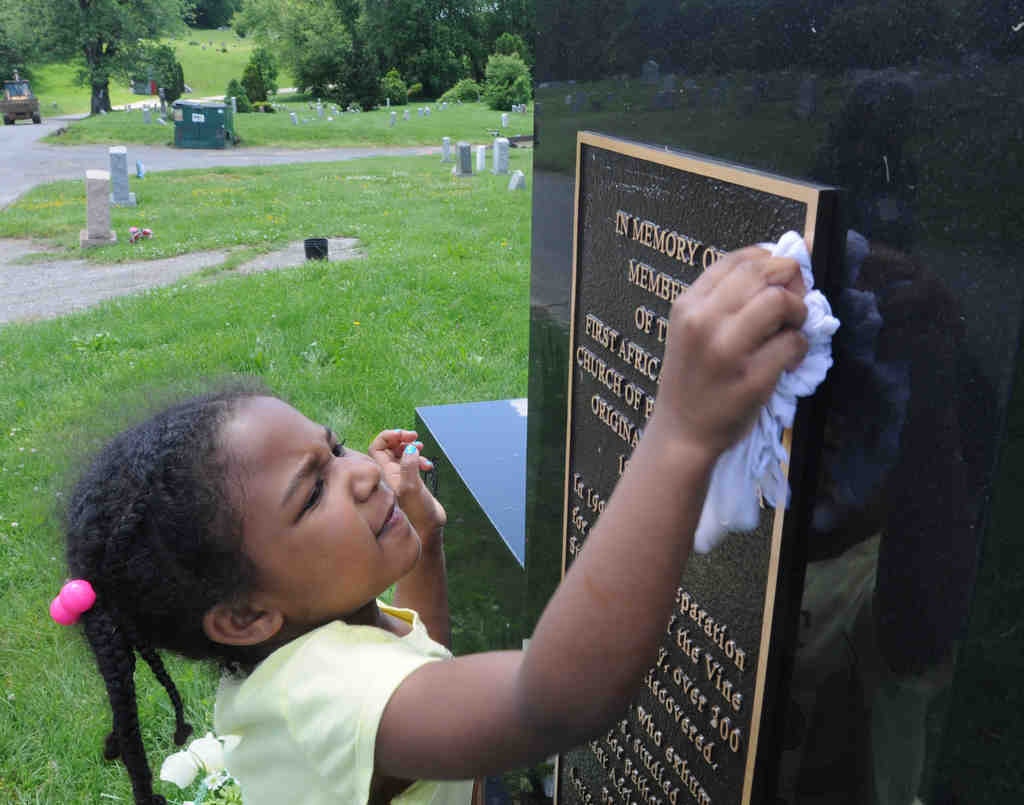 At historic Eden Cemetery in Collingdale, volunteers on Saturday helped clean up the resting places of hundreds of notable African Americans. Kymberli Napper Preston, 5, cleaned a tombstone.