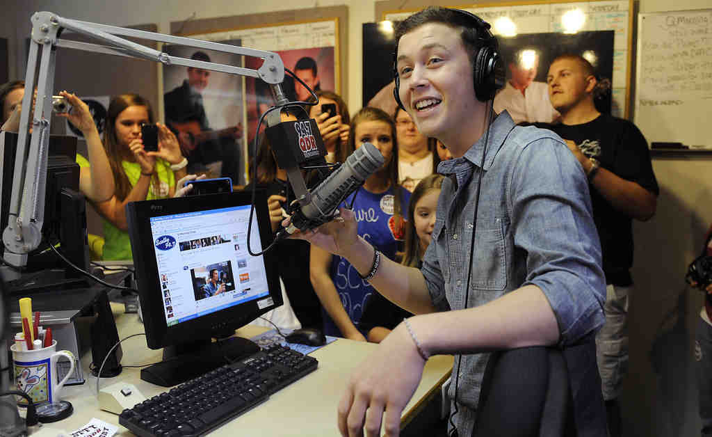 """Hometown heroes: """"American Idol"""" finalist Scotty McCreery, above, took to the microphone at a radio station during a visit to Raleigh, N. C. Below, Lauren Alaina greeted fans in Chattanooga, Tenn. The two have survived to the season´s final hours, and the new Idol will be announced Wednesday night."""